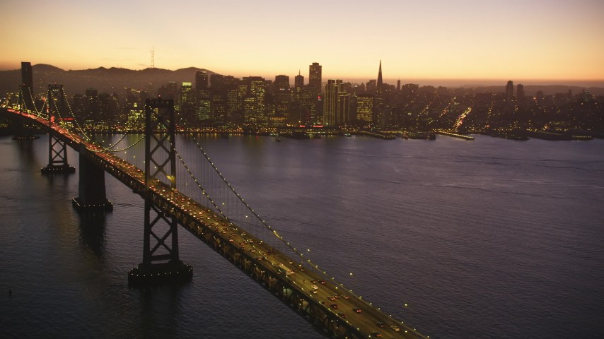5K stock footage aerial video of a reverse view of the Bay Bridge and skyline of Downtown San Francisco, California, twilight Aerial Stock Footage DFKSF10_086 | Axiom Images
