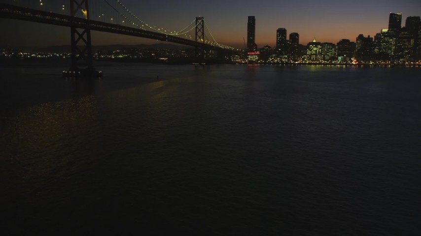 5K stock footage aerial video of flying by Bay Bridge, pan to Downtown San Francisco skyline, California, night Aerial Stock Footage | DFKSF10_094