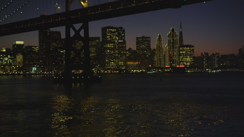 5K stock footage aerial video of approaching the Bay Bridge and the skyline of Downtown San Francisco, California, night Aerial Stock Footage | DFKSF10_099
