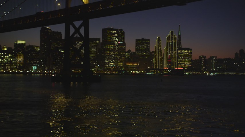 5K stock footage aerial video of flying under the Bay Bridge toward Ferry Building and skyscrapers in Downtown San Francisco, California, night Aerial Stock Footage | DFKSF10_100