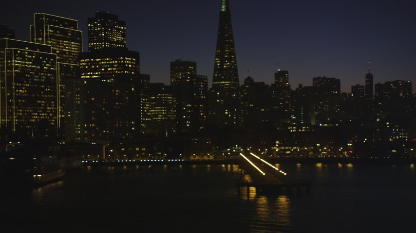 5K stock footage aerial video of flying low by piers and skyscrapers in Downtown San Francisco, California, night Aerial Stock Footage | DFKSF10_102