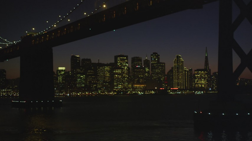 5K stock footage aerial video fly away from city skyline, reveal and fly under Bay Bridge, Downtown San Francisco, California, night Aerial Stock Footage | DFKSF10_104