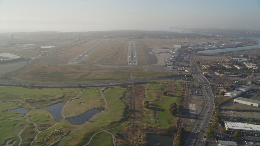 5K stock footage aerial video tilt from golf course to reveal and approach Oakland International Airport, California Aerial Stock Footage | DFKSF12_042
