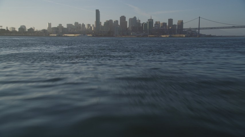 5K stock footage aerial video of flying low over bay, tilt up to reveal Downtown San Francisco skyline, California Aerial Stock Footage | DFKSF13_010