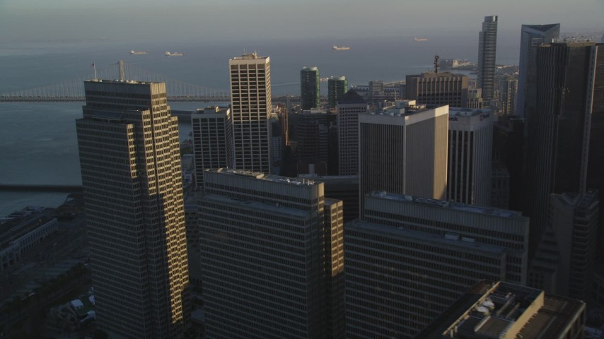 5K stock footage aerial video flyby downtown skyscrapers, reveal Bay Bridge in Downtown San Francisco, California Aerial Stock Footage | DFKSF13_059