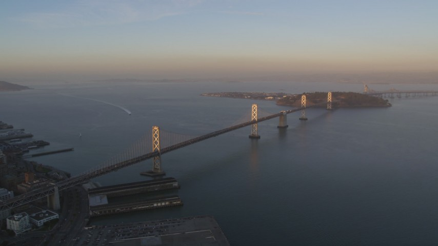 5K stock footage aerial video of flying by the Bay Bridge, San Francisco, California, sunset Aerial Stock Footage | DFKSF14_001