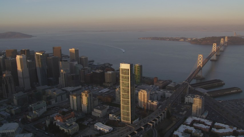 5K stock footage aerial video flyby Bay Bridge and One Rincon Hill skyscraper, reveal Downtown San Francisco, California, sunset Aerial Stock Footage | DFKSF14_002