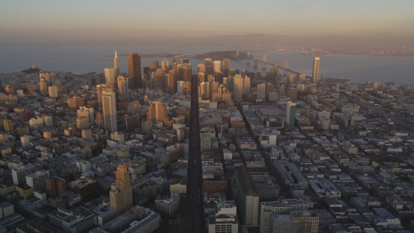 5K stock footage aerial video of flying by Market Street and skyscrapers in Downtown San Francisco, California, sunset Aerial Stock Footage | DFKSF14_003