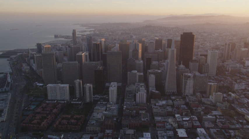 5K stock footage aerial video approach city skyscrapers, tilt to city streets below in Downtown San Francisco, California, sunset Aerial Stock Footage | DFKSF14_008