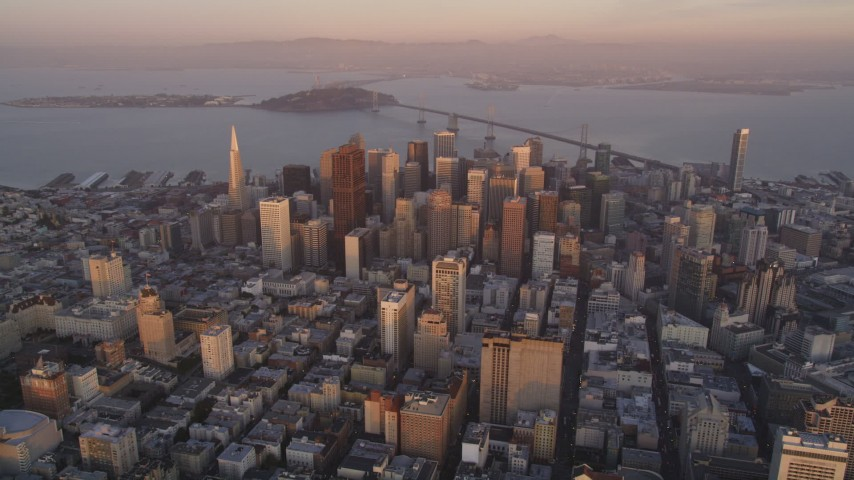 5K stock footage aerial video of flying away from city buildings and skyscrapers in Downtown San Francisco, California, sunset Aerial Stock Footage | DFKSF14_011