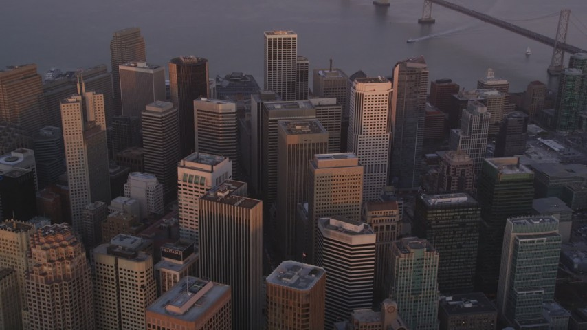 5K stock footage aerial video tilt from city skyscrapers to reveal Bay Bridge, Downtown San Francisco, California, sunset Aerial Stock Footage DFKSF14_016 | Axiom Images