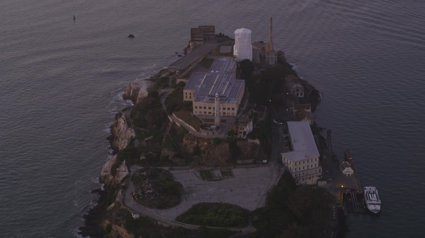 Fly by main buildings, lighthouse, Alcatraz, San Francisco, California, sunset Aerial Stock Footage | DFKSF14_022