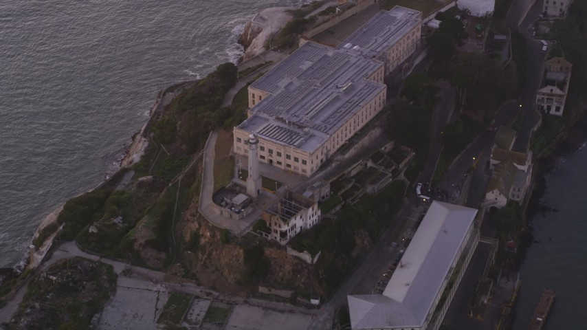 Flying over main buildings, lighthouse, Alcatraz, San Francisco, California, sunset Aerial Stock Footage | DFKSF14_023