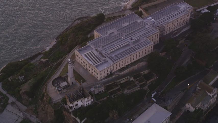 5K stock footage aerial video of passing the main buildings and lighthouse on Alcatraz, San Francisco, California, twilight Aerial Stock Footage | DFKSF14_023