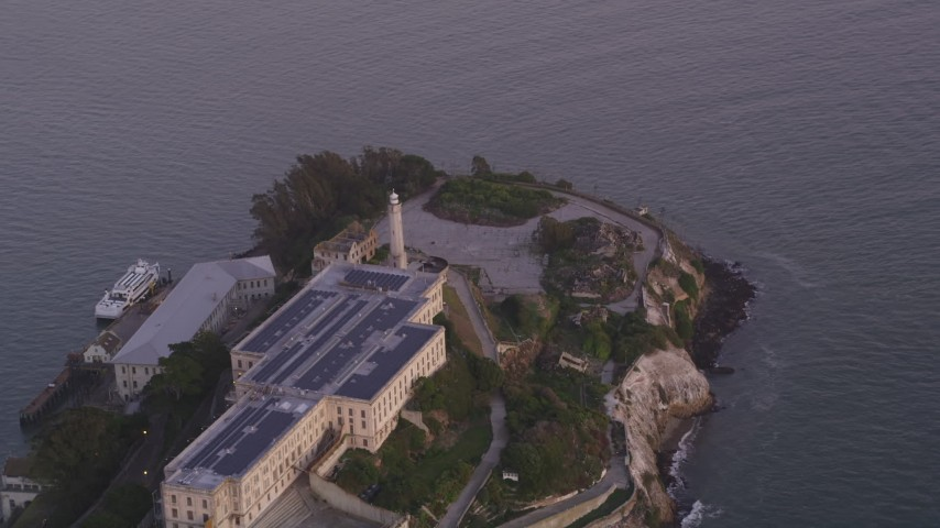 Flying by main buildings, lighthouse, Alcatraz, San Francisco, California, sunset Aerial Stock Footage | DFKSF14_024