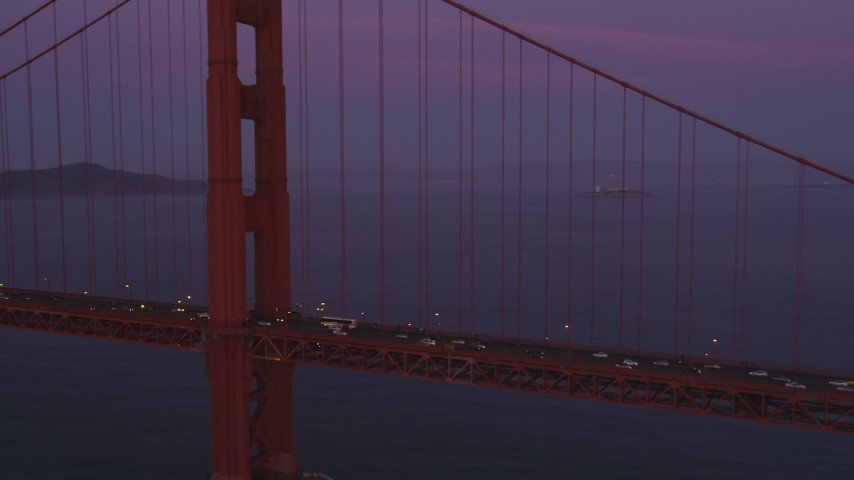 Fly over Golden Gate Bridge, reveal cargo ship, San Francisco, California, sunset Aerial Stock Footage | DFKSF14_042