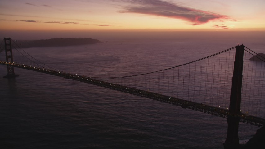 5K aerial video of flying by the iconic Golden Gate Bridge with traffic, San Francisco, California, twilight Aerial Stock Footage | DFKSF14_051