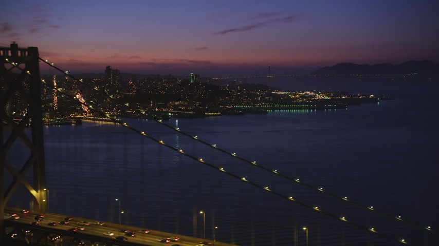 5K stock footage aerial video of flying over Bay Bridge while focusing on Coit Tower, North Beach, San Francisco, California, twilight Aerial Stock Footage | DFKSF14_074