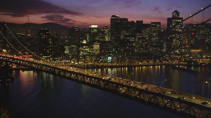 5K stock footage aerial video flyby Bay Bridge at twilight, revealing Downtown San Francisco skyscrapers, California, twilight Aerial Stock Footage | DFKSF14_076
