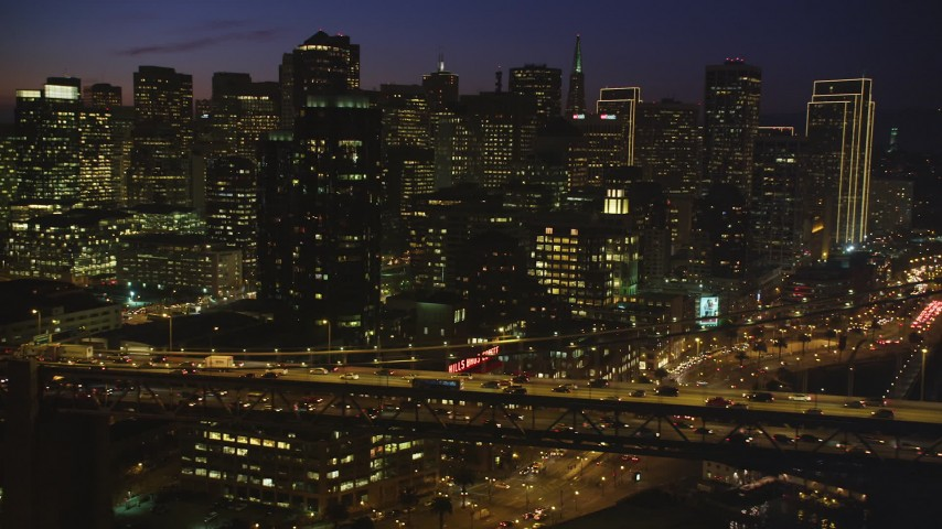 5K stock footage aerial video of flying by Bay Bridge, with views of Downtown San Francisco skyscrapers, California, night Aerial Stock Footage | DFKSF14_077