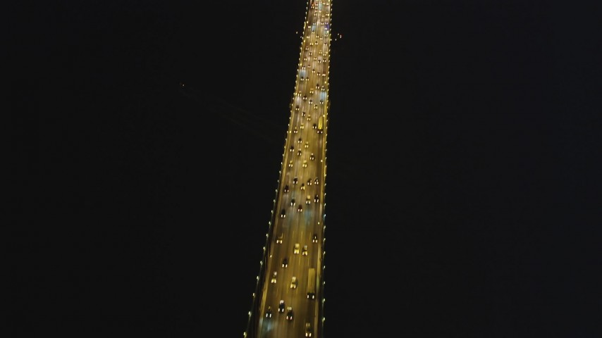 5K stock footage aerial video tilt from bird's eye of traffic to fly over the Bay Bridge, San Francisco, California, night Aerial Stock Footage | DFKSF14_081