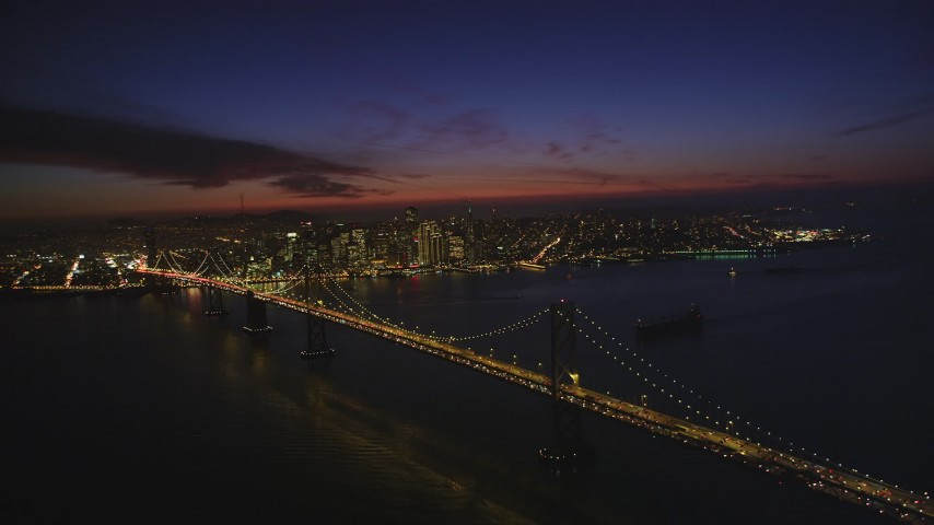 5K stock footage aerial video of flying by the Bay Bridge, with a view of Downtown San Francisco skyscrapers, California, night Aerial Stock Footage | DFKSF14_082
