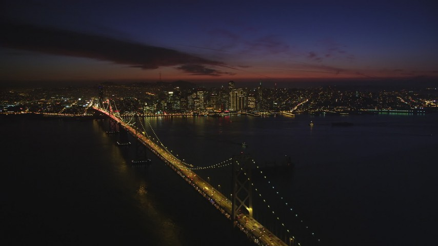 5K aerial video descend near Bay Bridge, with views of skyscrapers in Downtown San Francisco, California, night Aerial Stock Footage | DFKSF14_084