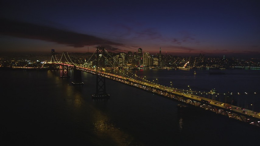 5K stock footage aerial video flyby the Bay Bridge, with views of skyscrapers in Downtown San Francisco, California, night Aerial Stock Footage | DFKSF14_085