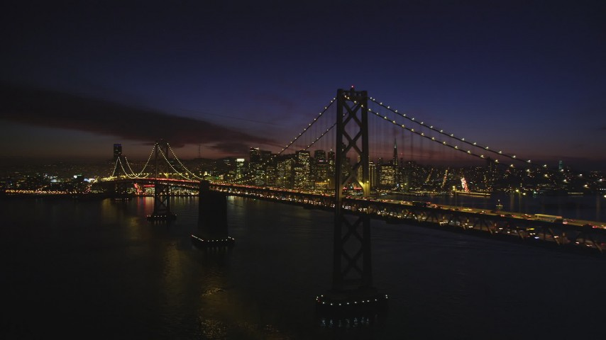 5K stock footage aerial video of the Bay Bridge, with views of Downtown San Francisco skyscrapers, California, night Aerial Stock Footage | DFKSF14_086