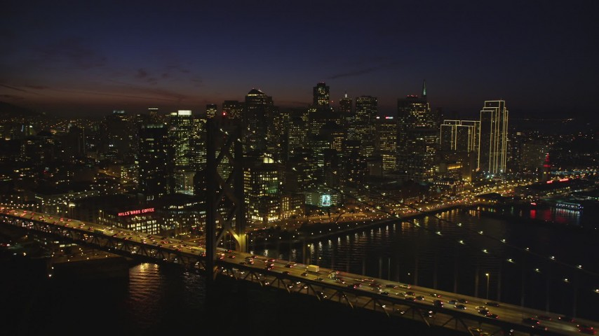 5K stock footage aerial video of flying by the Bay Bridge with a view of skyscrapers in Downtown San Francisco, California, night Aerial Stock Footage | DFKSF14_088