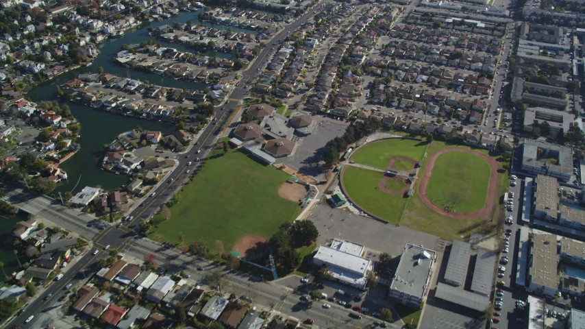 5K stock footage aerial video of a reverse view of suburban neighborhoods and baseball fields, Alameda, California Aerial Stock Footage | DFKSF15_002