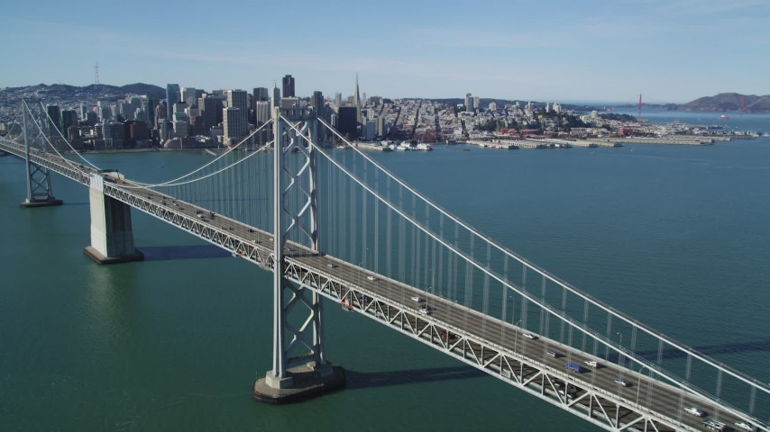 5K stock footage aerial video of flying over the Bay Bridge and panning to Downtown San Francisco skyline, California Aerial Stock Footage | DFKSF15_007