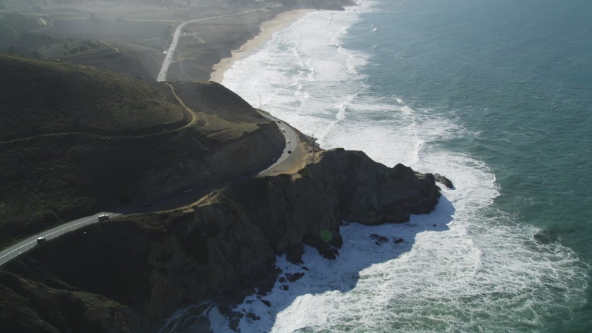 5K stock footage aerial video of flying over Highway 1 traffic winding above coastal cliffs, Montara, California Aerial Stock Footage | DFKSF15_061