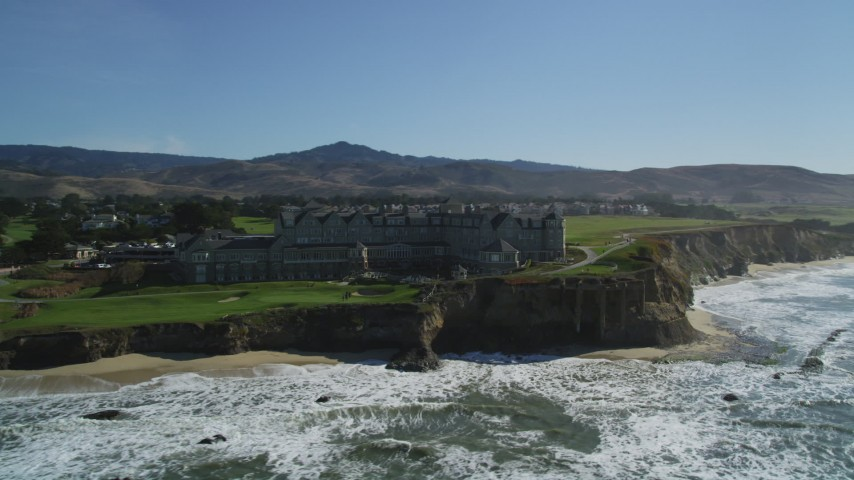 5K stock footage aerial video of flying by an oceanfront hotel on coastal cliffs, Half Moon Bay, California Aerial Stock Footage | DFKSF15_074