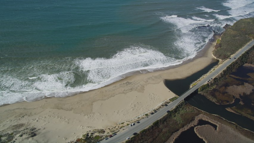 5K stock footage aerial video flyby the Highway 1 coastal road, revealing a beach, Davenport, California Aerial Stock Footage | DFKSF15_110