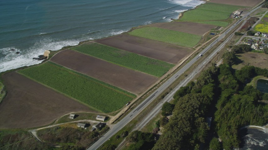 5K stock footage aerial video of flying away from Highway 1 along the coast and crop fields, Davenport, California Aerial Stock Footage | DFKSF15_113
