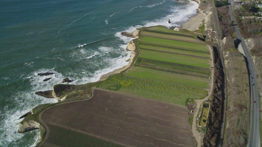 5K stock footage aerial video of a reverse view of Highway 1, train tracks and crop fields, Davenport, California Aerial Stock Footage | DFKSF15_114
