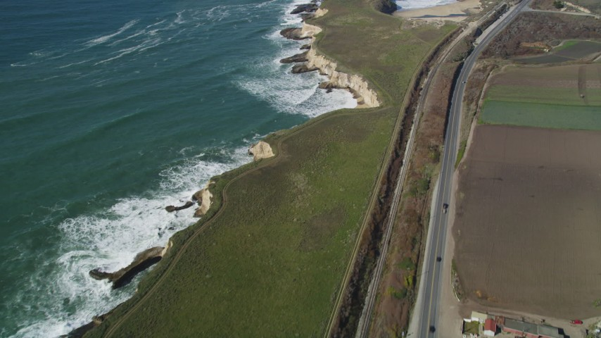 5K stock footage aerial video of a reverse view of Highway 1 coastal road and train tracks, Davenport, California Aerial Stock Footage | DFKSF15_115