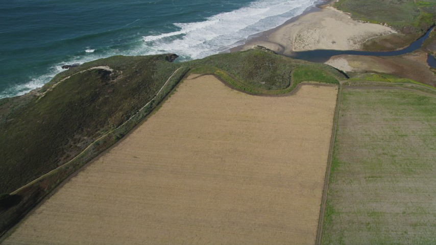 5K stock footage aerial video of a reverse view of farm fields on the coast, Santa Cruz, California Aerial Stock Footage | DFKSF15_117