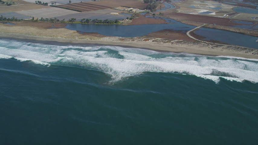 5K stock footage aerial video of flying by waves rolling toward a beach, Moss Landing, California Aerial Stock Footage | DFKSF15_146