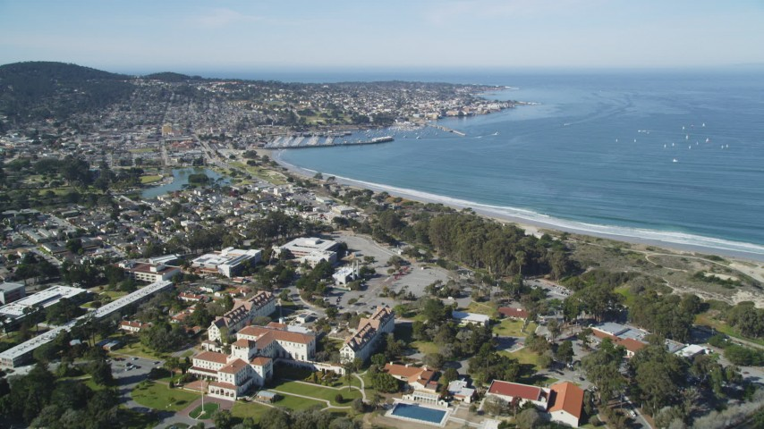 5K stock footage aerial video tilt from highway interchange, reveal US Naval Postgraduate School and coastal community in Monterey, California Aerial Stock Footage | DFKSF16_003