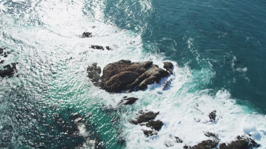 5K stock footage aerial video tilt from waves crashing into rock formations to reveal Cypress Point Golf Course, Pebble Beach, California Aerial Stock Footage | DFKSF16_019