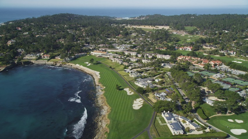 5K stock footage aerial video of passing by an oceanfront resort hotel and golf course in Pebble Beach, California Aerial Stock Footage | DFKSF16_029