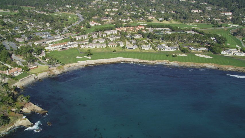 5K stock footage aerial video tilt from Carmel Bay, reveal a resort hotel and golf course, Pebble Beach, California Aerial Stock Footage | DFKSF16_032