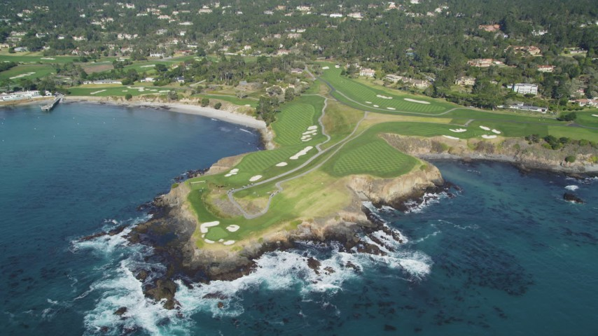 5K stock footage aerial video tilt from the ocean to reveal a golf course on the coast in Pebble Beach, California Aerial Stock Footage | DFKSF16_033