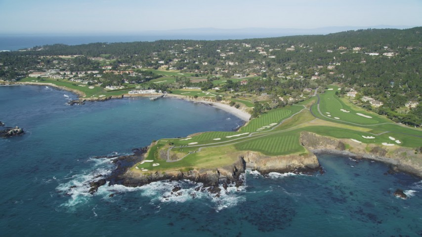 5K stock footage aerial video of a reverse view of a resort hotel and golf course by Carmel Bay, Pebble Beach, California Aerial Stock Footage | DFKSF16_034