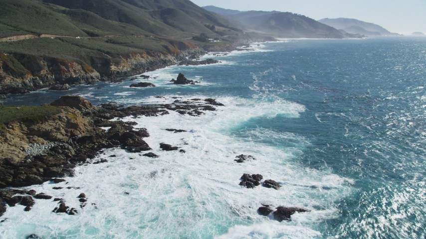 5K stock footage aerial video of flying over the waves rolling toward the coastal cliffs, Carmel, California Aerial Stock Footage | DFKSF16_057