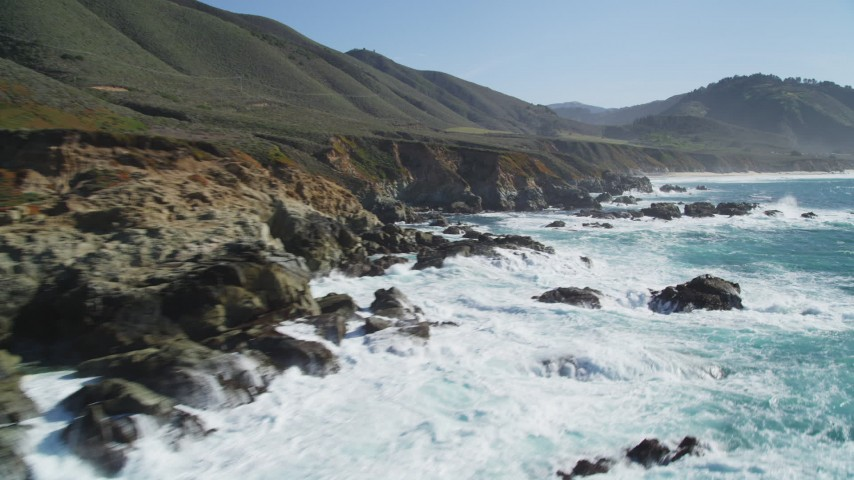 5K stock footage aerial video of flying over waves crashing into the coastal cliffs and rock formations, Carmel, California Aerial Stock Footage | DFKSF16_060