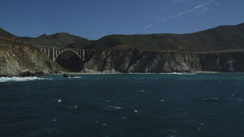 5K stock footage aerial video of flying by coastal rock formation, revealing Bixby Creek Bridge, Big Sur, California Aerial Stock Footage | DFKSF16_072