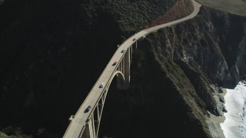 5K aerial video of light traffic on the Bixby Creek Bridge above coastal cliffs, Big Sur, California Aerial Stock Footage | DFKSF16_075